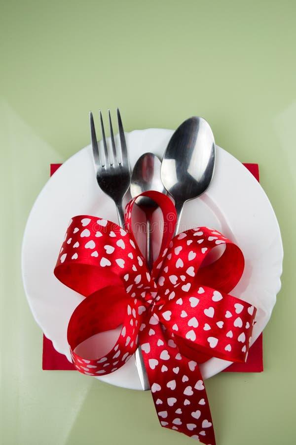 Walentynka dnia stołu położenie z talerzem, rozwidleniem, czerwonym faborkiem i sercami, zdjęcia royalty free
