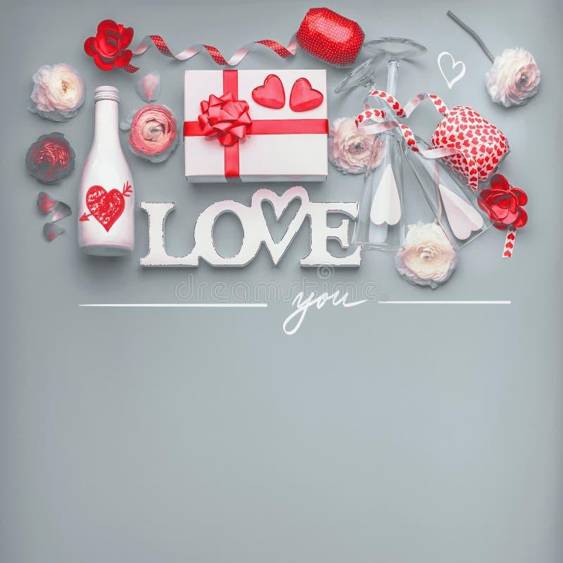 Walentynka dnia tło Świąteczny skład robić z kwiatami, prezenta pudełkiem i czerwonym łękiem miłość, butelka szampan z szkłami zdjęcie royalty free