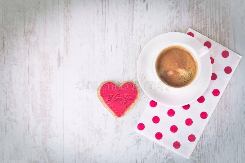 Walentynka dnia tło Odgórny widok kierowy kształtny ciastko i filiżanka kawy nad białym drewnianym nieociosanym tłem zdjęcia royalty free