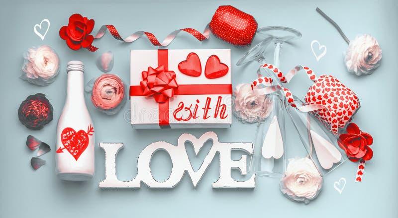 Walentynka dnia układ Świąteczny skład robić z kwiatami, prezenta pudełkiem i czerwonym łękiem miłość, butelka szampan z szkłami, zdjęcie royalty free