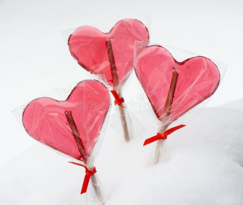 Walentynka dzień - czerwoni kierowi lizaki na śnieżnym tle obraz royalty free
