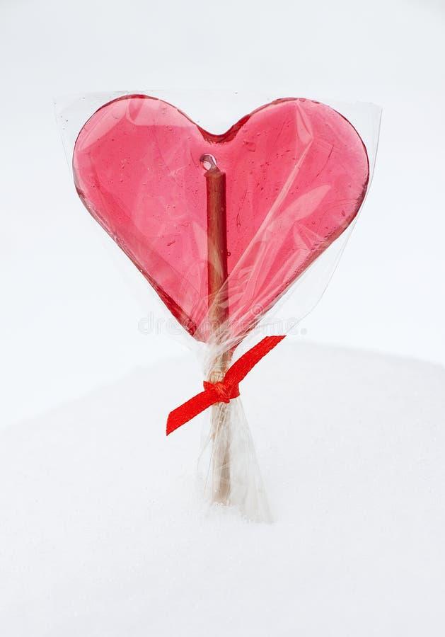 Walentynka dzień - czerwony kierowy lizak na śnieżnym tle zdjęcia royalty free