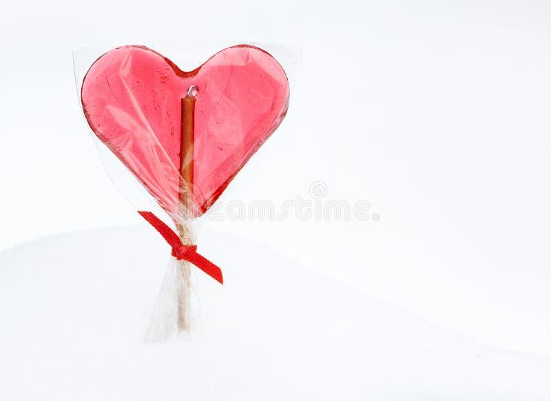 Walentynka dzień - czerwony kierowy lizak na śnieżnym tle obrazy royalty free