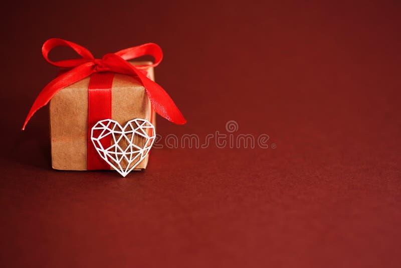 Walentynka dzień, Kraft papieru prezenta pudełko z białym drewnianym sercem na czerwonym tle obraz stock