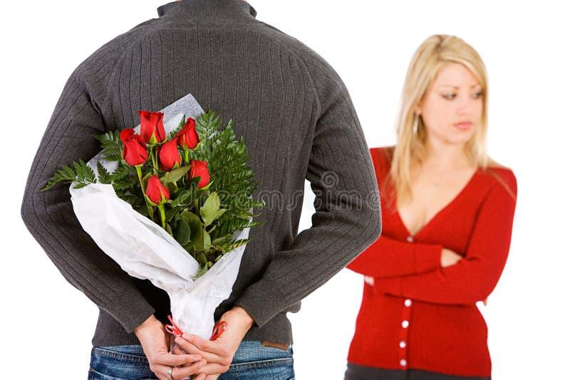 Walentynka: Mężczyzna Przynosi kobieta kwiaty Przepraszać obrazy royalty free
