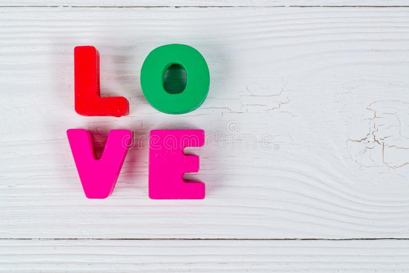 Walentynki karta z miłość tekstem na białym drewnianym policjancie i tle fotografia royalty free