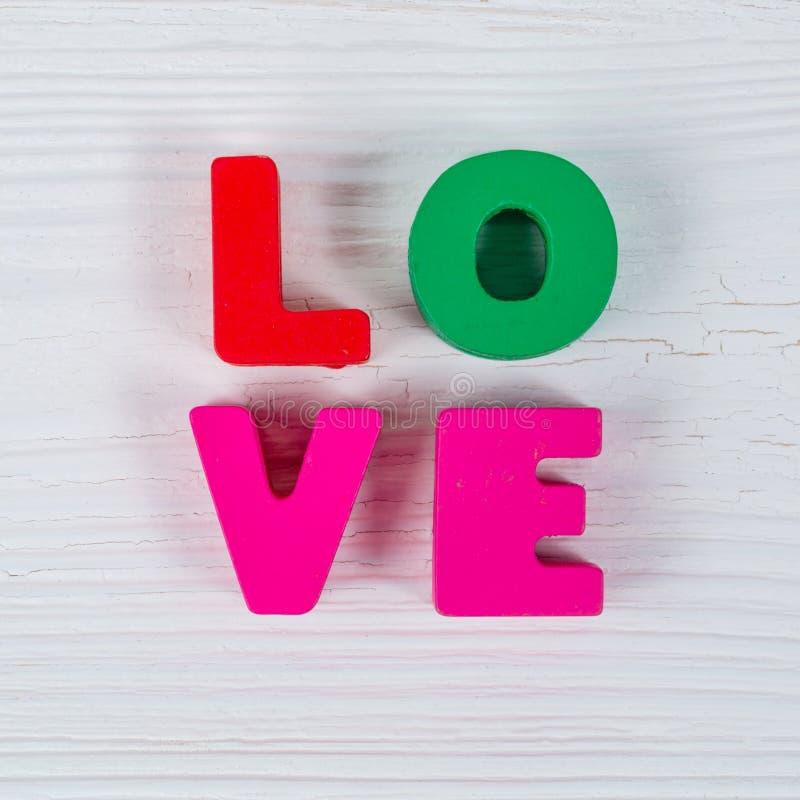 Walentynki karta z miłość tekstem na białym drewnianym policjancie i tle obraz stock