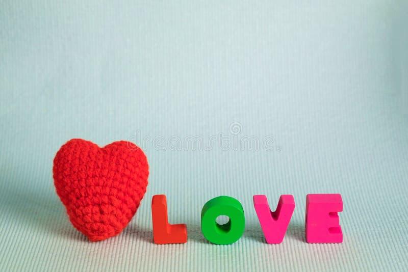 Walentynki karta z miłości czerwieni i teksta dziewiarskim sercem na błękitnym bac zdjęcia stock