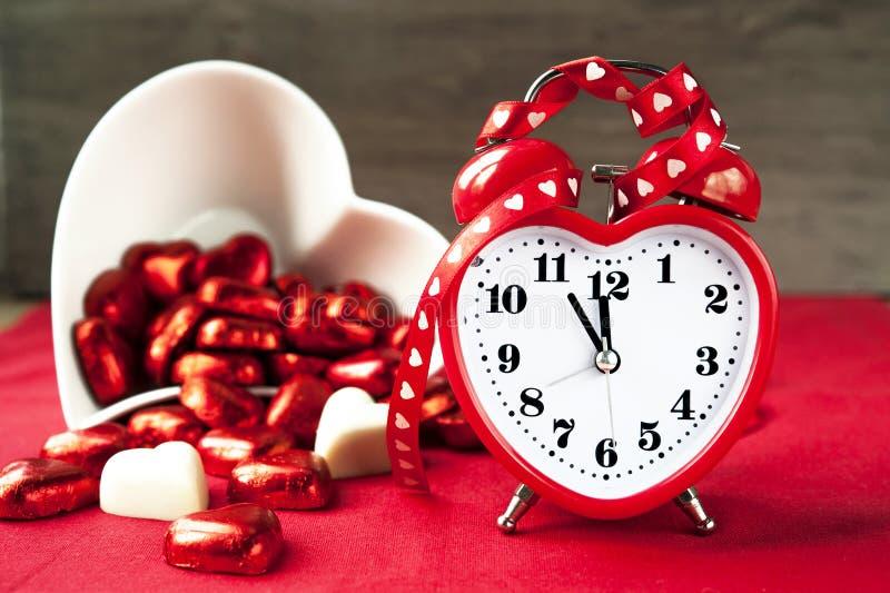 Walentynki miłości miłości kierowy kształtny czerwony zegar z słodkimi czekoladami fotografia stock