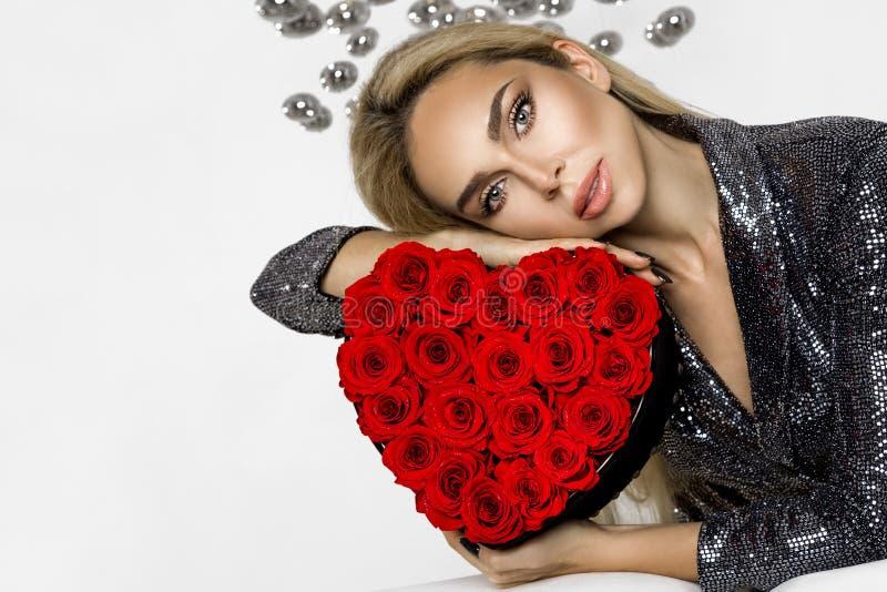 Walentynki piękna dziewczyna z czerwonymi kierowymi różami Portret młody kobieta model z prezentem, odizolowywający na tle obraz stock