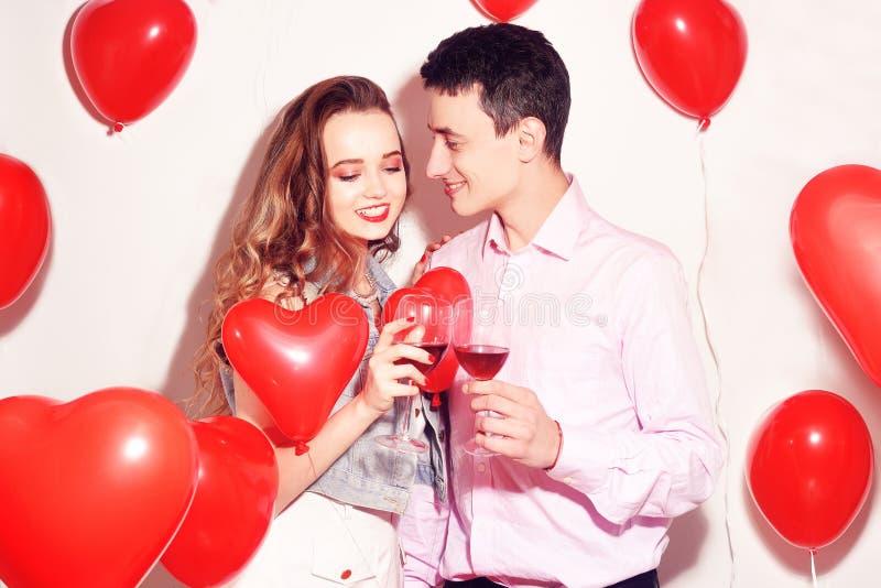 Walentynki piękna para pije czerwone wino z czerwonym lotniczych balonów sercem Piękni Szczęśliwi młodej kobiety i mężczyzny uści fotografia stock