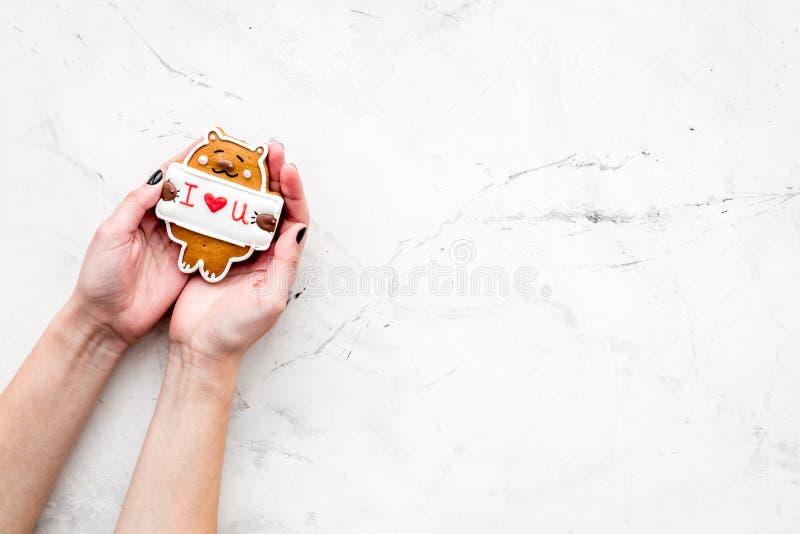 Walentynki ` s dnia cukierek Ciastko w kształcie niedźwiedź z literowaniem kocham ciebie w rękach na jasnopopielatego tła odgórny fotografia royalty free