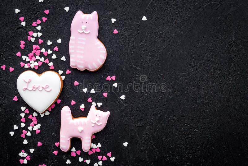 Walentynki ` s dnia cukierek Serce kształtujący ciastko z literowanie kiciunią na czarnej tło odgórnego widoku kopii przestrzeni  zdjęcie stock