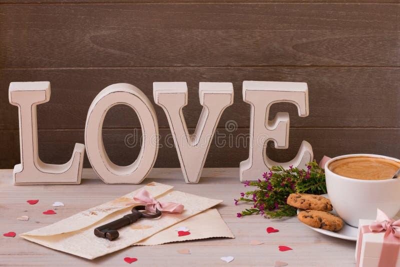 Walentynki ` s dnia dekoraci zakończenie up Filiżanka kawy, prezenty, kwiaty i słowo miłość na drewnianym tle, Klucz od twój serc obraz stock