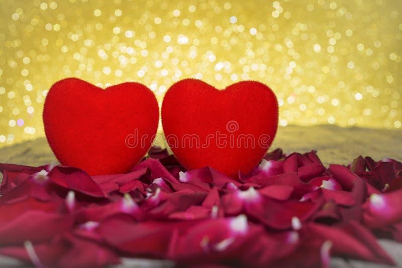 Walentynki ` s dnia tło, czerwoni serca i płatki na stole, błyskotliwości tło obrazy royalty free