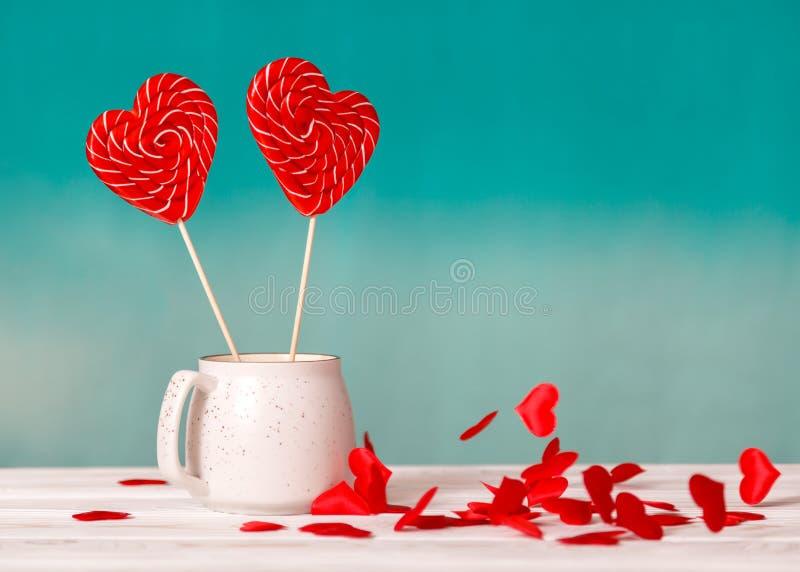 Walentynki ` s dnia tło Dwa lizak w kierowym kształcie w białej filiżance na błękitnym tle spada małych sercach i obraz stock
