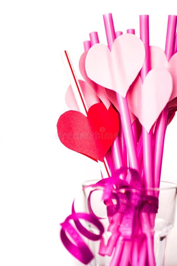 Walentynki ` s dnia wakacje jaskrawe różowe pije słoma z sercami i różowy faborek w szkle odizolowywającym na bielu fotografia stock