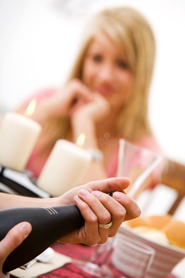 Walentynki ` s: Kobiet czekania Jako mężczyzna Otwierają Szampańską butelkę zdjęcia stock