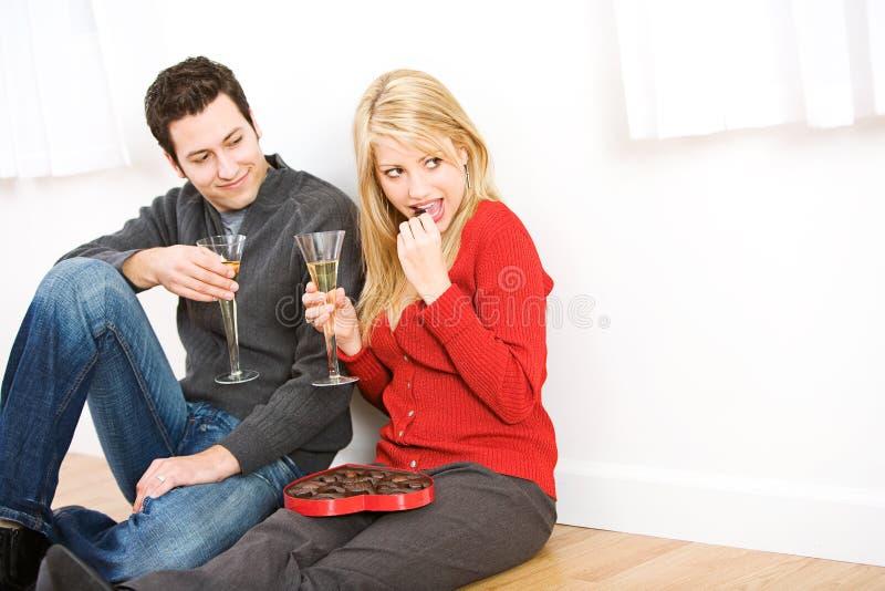 Walentynki ` s: Pary obsiadanie Na Podłogowej łasowanie czekoladzie, Drink i fotografia royalty free