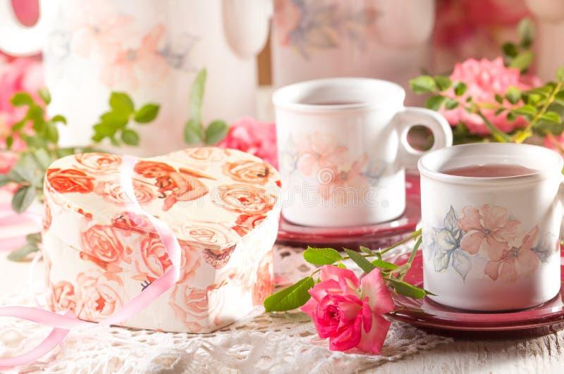 Walentynki tło, dwa filiżanki, różowe róże, prezenta pudełko zdjęcie royalty free