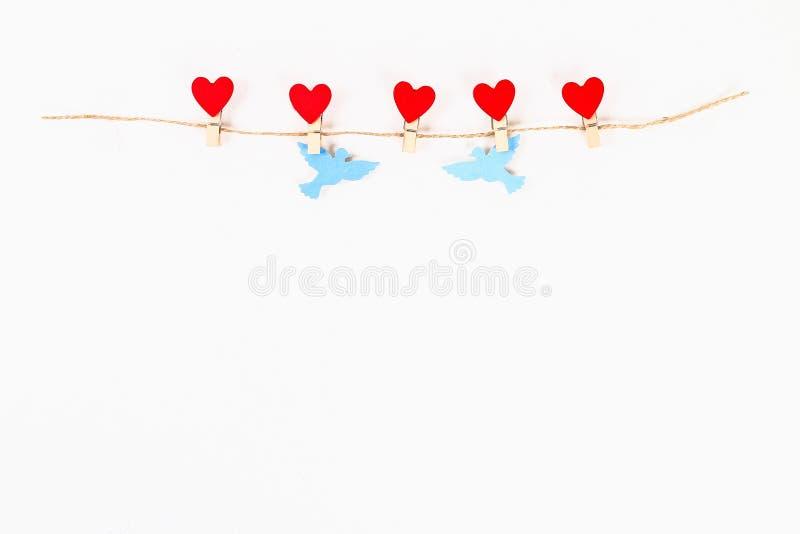 Walentynki układ Czerwona serca i gołąbek miłość na drewnianych clothespins na jutowej dratwie na białym tle St walentynek dzień, obrazy stock