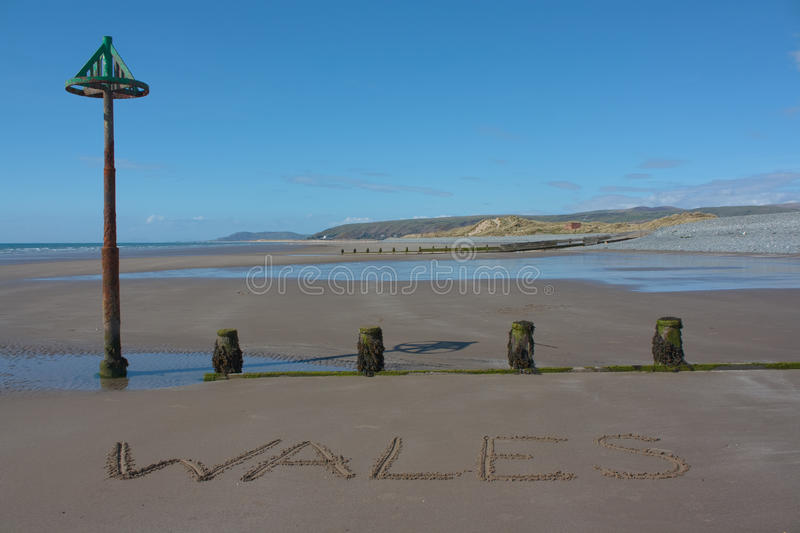 Wales on beach. The name Wales on the beach at Borth stock image