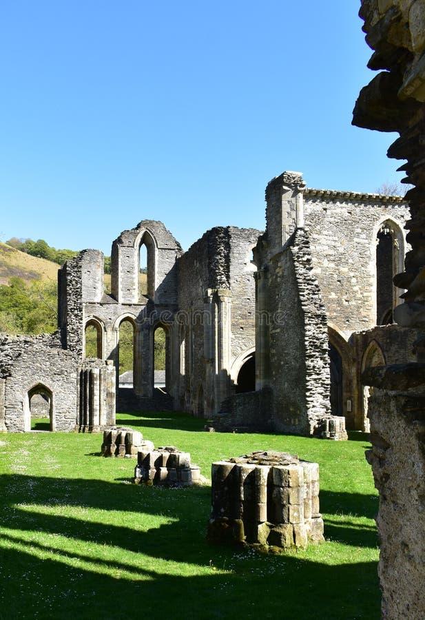 Wales, den Valle Crucis abbotskloster, en ljus vårdag med solbelysta väggar och skuggor royaltyfri bild