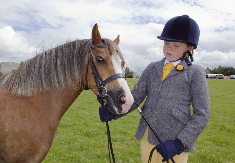 Waliser-Mädchen am Dressurreitenversuch im Schutzhelm mit Pony lizenzfreies stockfoto
