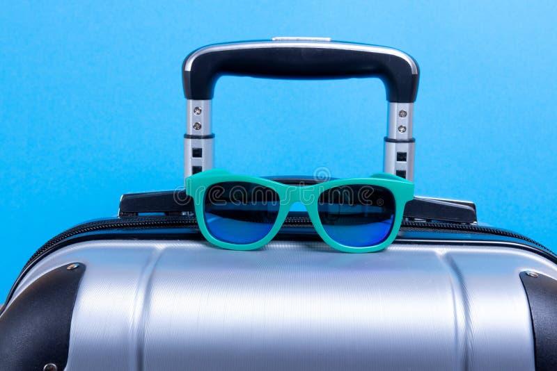 Walizka bagaż dla ręka okularów przeciwsłonecznych na błękitnym tle i bagażu Pojęcie podróż na wakacje obraz royalty free