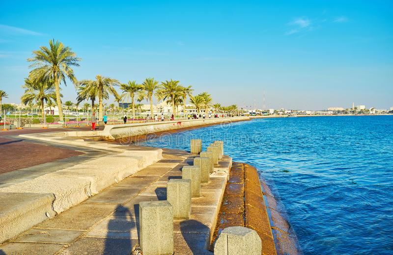 Pleasant walk in Doha, Qatar. The walk along the shore of Persian Gulf, the Corniche promenade of Doha is popular walking zone, Qatar royalty free stock photo