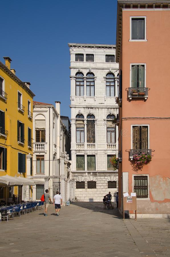 Tourists are walking the street along the old houses in Venice stock photography