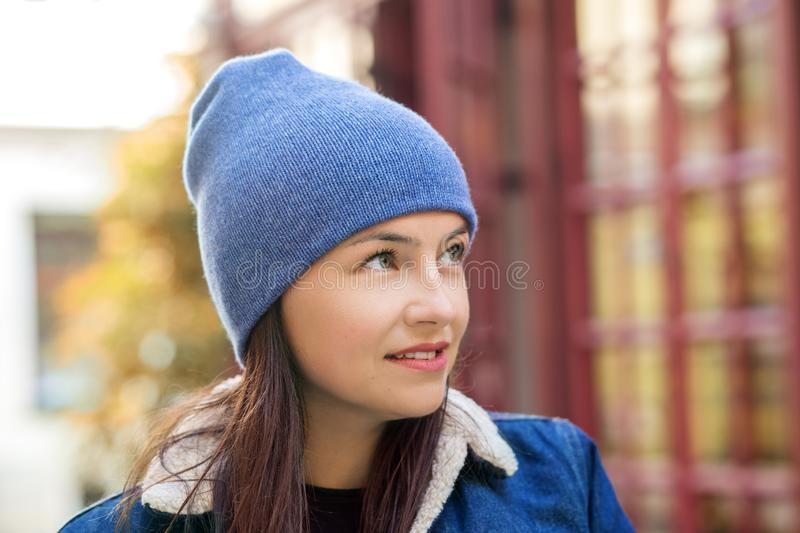 Walk around the city in cold weather. Woman in a blue hat. Concept lifestyle, autumn. Urban royalty free stock image