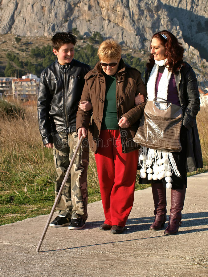 Walk with the blind woman. Grandson and daughter take with hands (holding) a blind woman while walking with white stick in a sunny spring day. Vertical color royalty free stock photos