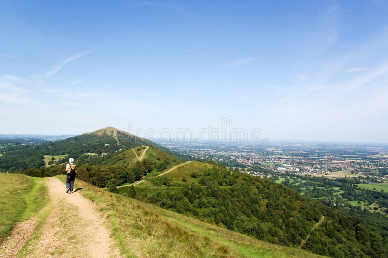 Walk the hills. Woman walker on hill top track on bright sunny summers day royalty free stock photo