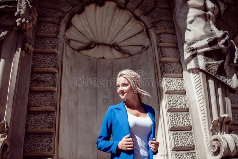 Walk through historic center. Beautiful girl, blonde with a ponytail in a blue pantsuit, against historical buildings. Walk through the historic center stock image