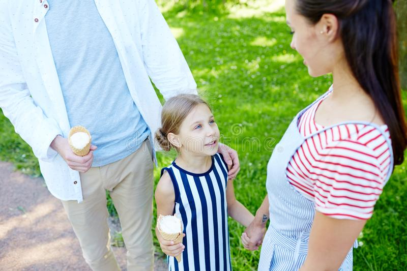 Walk with icecream. Cute girl with icecream talking to her mother while taking walk with parents on summer day stock photo