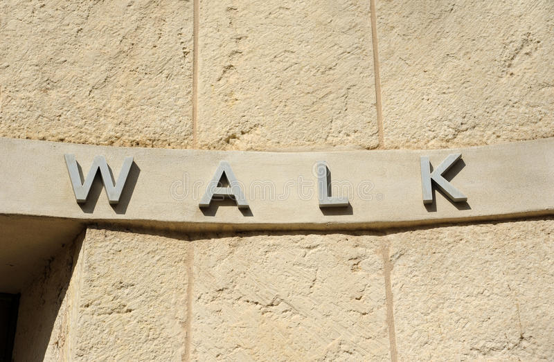 Walk Sign. On a Curved Stone Wall stock images