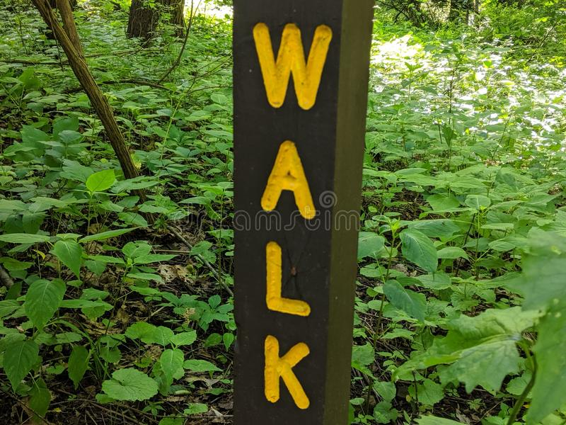 Walk sign, yellow letters on brown wood post. Hike, run, instruct, instructions, symbol, yield, warning, trail, path, hiking, hikers, walkers, walking stock images
