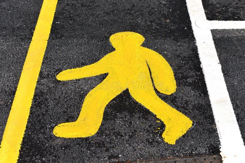 Walk sign. Yellow man walk sign on tarmac road royalty free stock image