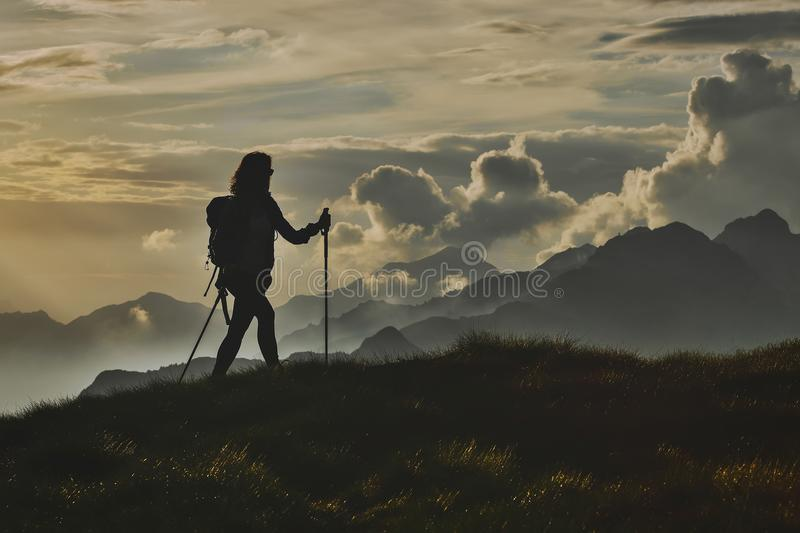 Walk in solitude on the Alps. A woman on with the background of. Abstract mountains in the clouds stock photo