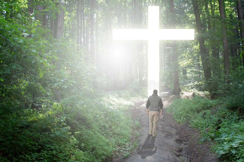 Walk to the Cross. Man walking to a Christian Cross of light royalty free stock photo