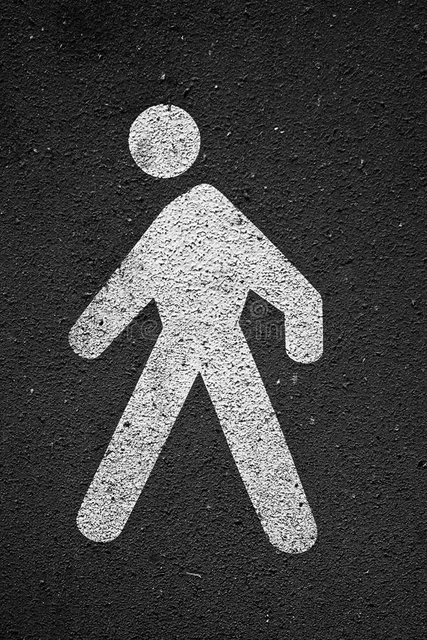 Walk traffic sign on the ground. Close-up photo of walk white traffic sign on the asphalt ground royalty free stock images