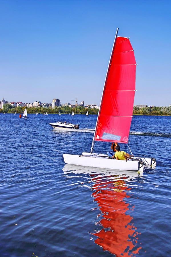 Walk under a sail on a catamaran. Sunny day, blue lake. royalty free stock images