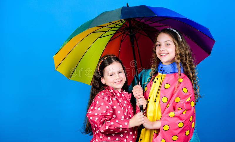 Walk under umbrella. Kids girls happy friends under umbrella. Rainy weather with proper garments. Happy childhood stock photos