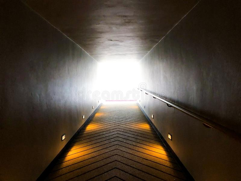 Walk way and hand holder beside forward to the light exit or light of hope royalty free stock photography