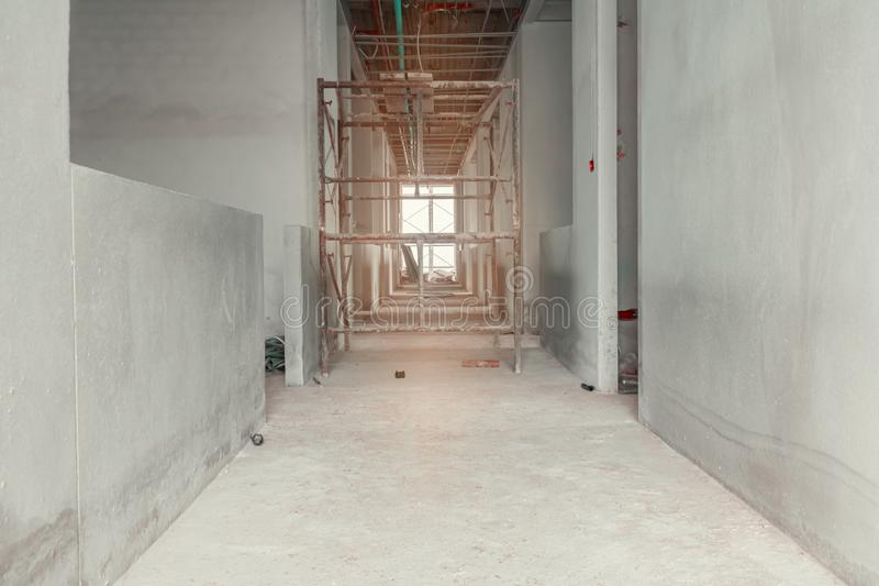 Walk way interior and scaffolding in construction building site with sun light tone.  royalty free stock photos