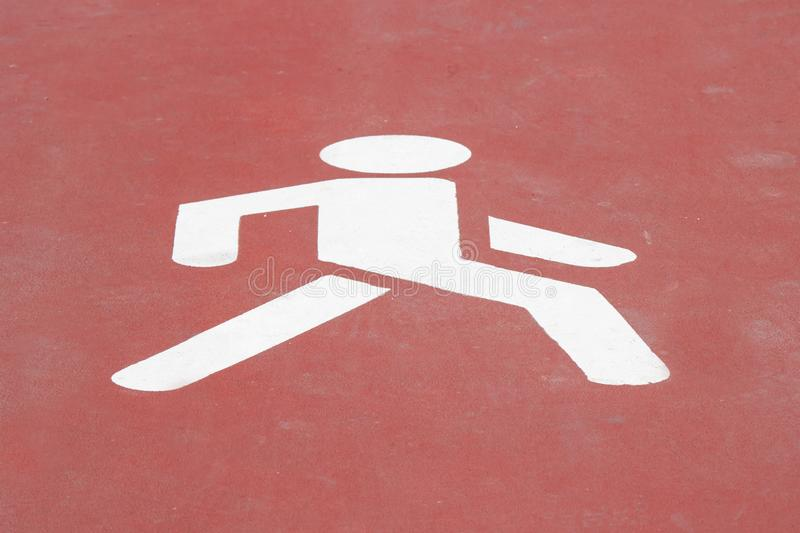 Walk way sign painted on the floor. Human icon walking on red background. Road, walkway, fitness, movement, health, graphic, signal, pedestrian, park stock images