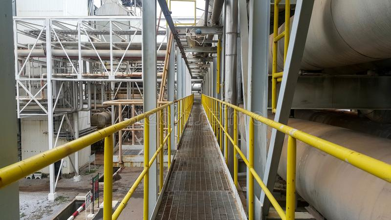 Walk way with yellow handrail inside factory stock photography