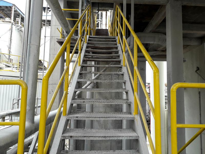 Walk way with yellow handrail inside factory royalty free stock photo