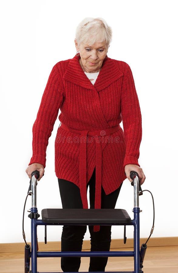 Walker. Elder disabled women is walking with walker stock image